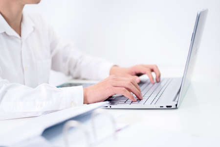 young man using laptop typing on keyboard.for writer journalist or working on computer at home. Businessman work from home, or online learning concept 版權商用圖片