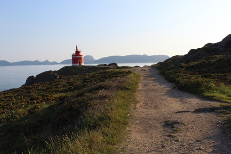 Red and white lighthouse in Punta Robaleira (Galicia, Spain), In the background are the islands C?es. Imagens