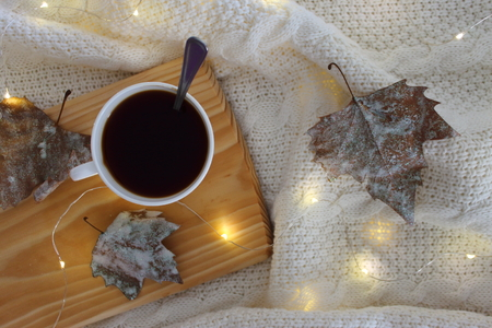 Winter coffee in house. Cup of coffee on bed with warm plaid, decorated leafs and lights. Copy space. Top view. 版權商用圖片
