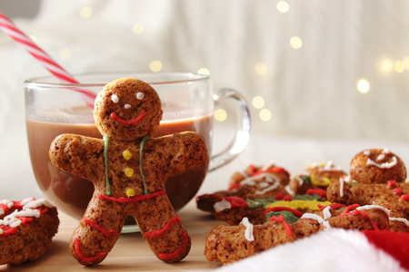 Smiling gingerbread man with cookies and defocused holiday lights in the background Stock Photo