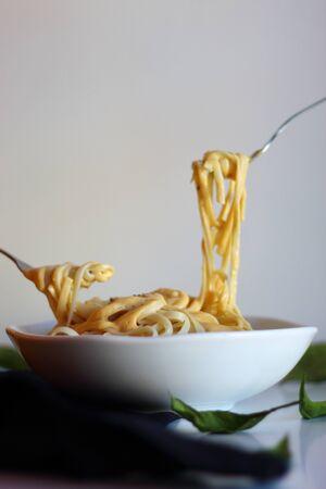 Eating pasta spaghetti with pumpkin-cream sauce. Autumn dish