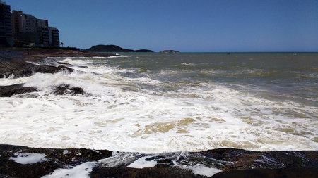 foaming: Rocks and rough sea foaming with buildings in the background