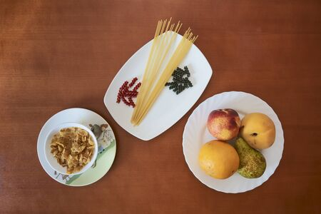 cereals, pasta and fruits on white plates and wooden table Фото со стока