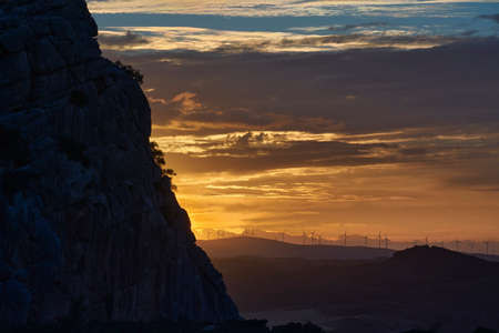 wind turbines at sunset and mountain silhouette in the Guadalteba region in Malaga. Spain