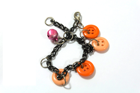 The chain braclet with colorful studs has a pink bell. On white background.