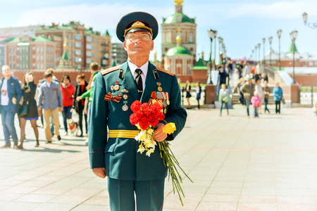 Yoshkar-Ola, Russia - May 9, 2015 Unknown veteran of World War II, standing with flowers on the street of Yoshkar-Ola, Russia Editöryel