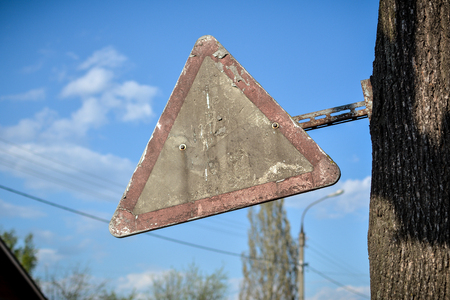 Old dirty post apocalyptic triangular road sign Stock Photo
