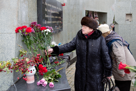 Yoshkar-Ola, Russia - October 30, 2017 Unknown woman lays flowers at the monument to the victims of political repression in Yoshkar-Ola, Russia