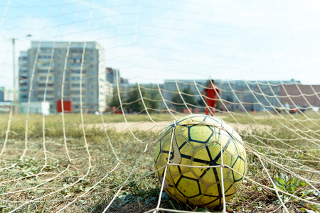 Yoshkar-Ola, Russia - August 20, 2016 A soccer ball in the net of a football goal during a game of street football in one of the streets of the city of Yoshkar-Ola Stock Photo - 92080203
