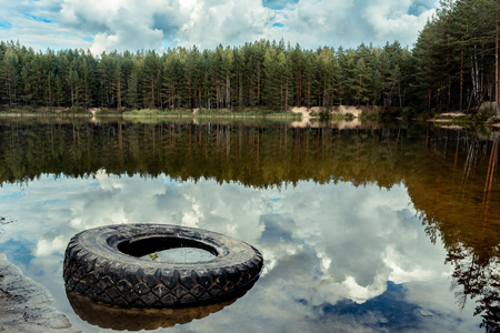 Old car tire on the lake shore Stock Photo