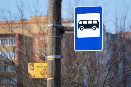 Photo of a bus stop sign on a concrete pillar in the city