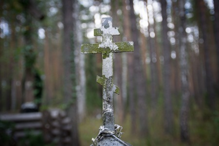 Old rusty metal Christian cross on an abandoned grave in the forest