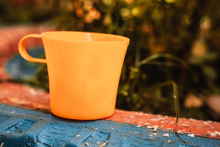 Yellow plastic cup to drink water, coffee, tea, outdoors