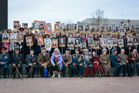 Yoshkar-Ola, Russia - April 28, 2015 Young cadets and veterans holds a portrait of his father as he takes part in the Immortal Regiment march