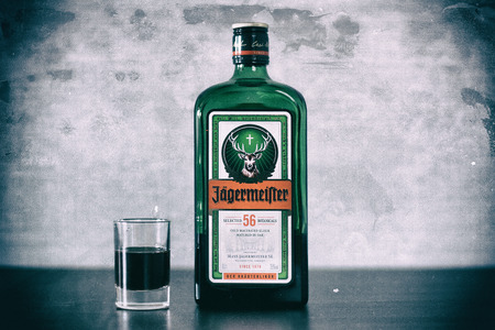 Yoshkar-Ola, Russia - December 19, 2017 Jagermeister, German digestif made with 56 herbs and spices is the flagship product of Mast-Jagermeister SE. Photo view from above. Retro Styling. Editorial