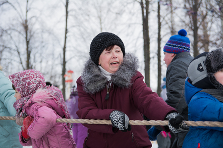 Yoshkar-Ola, Russia - February 26, 2016 Tug of war during the Carnival. Emotional portrait of a woman tugging on a rope.
