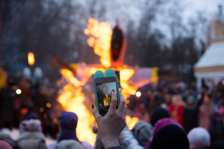 Yoshkar-Ola, Russia - February 18, 2018 Maslenitsa fest. Shooting a video on the phone burning stuffed carnival Imagens - 124658260