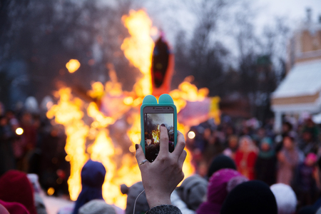 Yoshkar-Ola, Russia - February 18, 2018 Maslenitsa fest. Shooting a video on the phone burning stuffed carnival Editorial