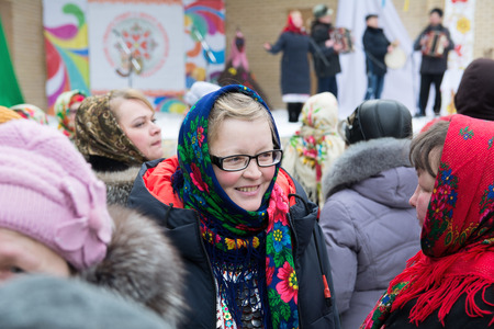 Yoshkar-Ola, Russia - February 18, 2018 Smiling girl in scarf Russian style at Shrovetide