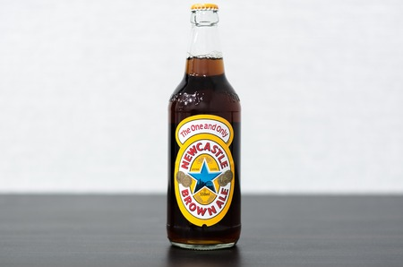 Yoshkar-Ola, Russia - February 19, 2018 A bottle of Newcastle Brown Ale. Launched in 1927 by Colonel Jim Porter after the merger of Newcastle Breweries with Scottish Brewers