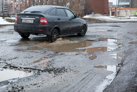 Yoshkar-Ola, Russia - April 4, 2016 Lada Priora car rides along the road with a terrible condition of asphalt covering Editorial