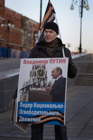 Yoshkar-Ola, Russia - March 18, 2015 Activist of the national liberation movement (NOD) with a poster Vladimir Putin - leader of the liberation movement during the rally on the anniversary of the annexation of the Crimea