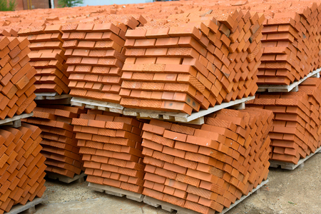 Red bricks stacked into cubes. red blocks of bricks in stock. Warehouse bricks. Bricks lie at an angle in diagonal lines