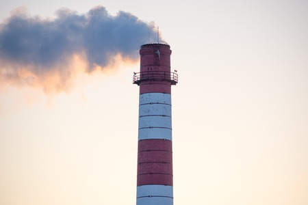 Chimney of a factory with white smoke and clear blue sky