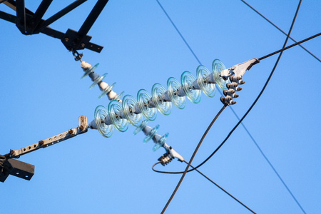 High-voltage electrical insulator electric line against the dark blue sky