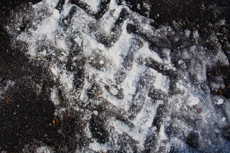 Texture of broken ice on asphalt. A good background of frozen water