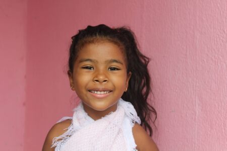 Portrait of cute little girl. She's got your old wooden door. African-American mixed race child.