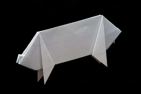 Origami of a pig against black background.