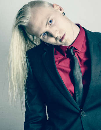 head tilted: Young fashionable handsome man with long blond hair in a suit. Head tilted over looking at the camera. Stock Photo