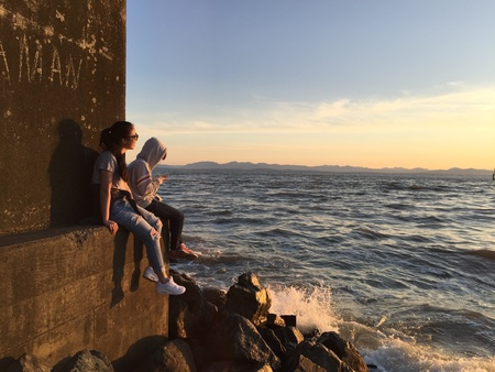 Two young women sitting on the edge of a brick wall at the shore