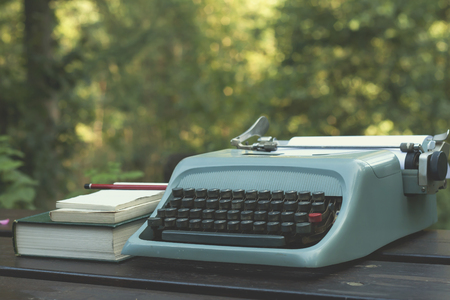 retro background: blie typewriter and books on a wooden garden table