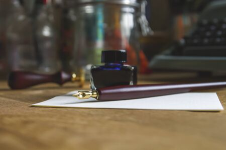 Paper, fountain pen and blue ink on the desk