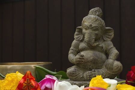 Ganesh decorative stone statue in the garden with flowers