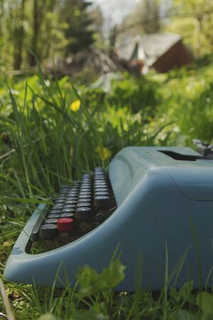 Old typewriter on the green garden grass