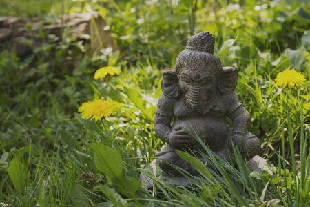 Lord Ganesh decorative stone statue in the green garden grass