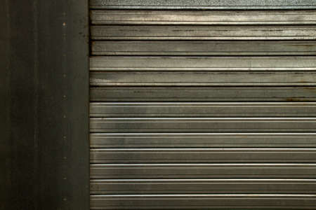 Metal shutter door in closed shop, abstract background or texture