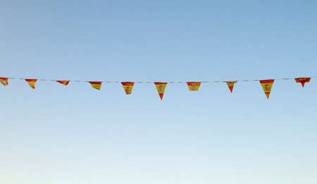 Spain plastic pennat flags and blue sky background