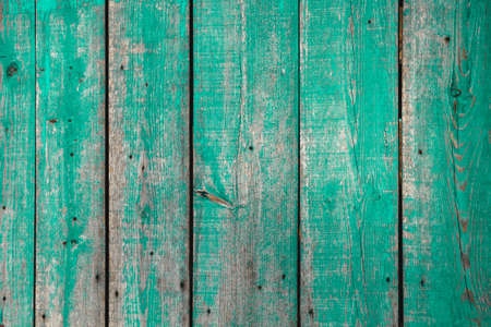 Old distressed rustic wooden planks wall with worn green paint, grunge wood texture or background