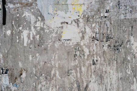 Old bulleting board wall with rests of worn peeled advertising posters, grunge background or texture