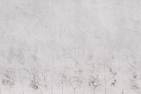 White paint peeling of the surface of a plaster wall, grunge background or texture