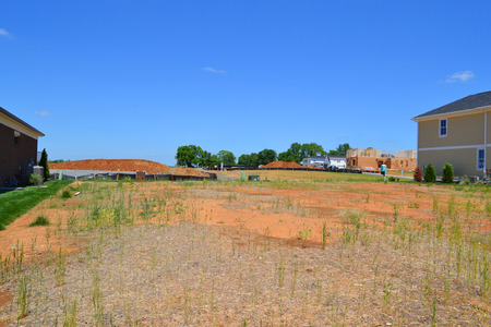 housing lot: Available Lot in a Brand New Suburban Housing Development in the Summertime Stock Photo