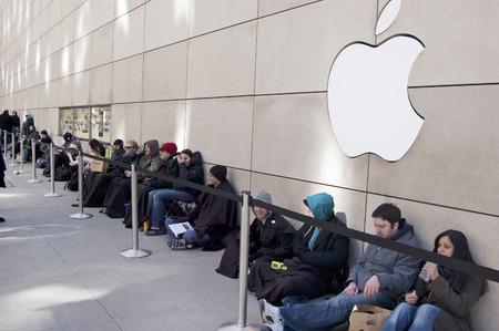 fila de personas: Los clientes esperar en la l�nea exterior de la tienda de Apple en la Michigan Avenue, en el centro de Chicago, Illinois Editorial