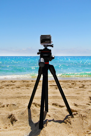 tripod mounted: GoPro HERO3  Black Edition Action Camera Mounted on a Tripod at a Beach Editorial