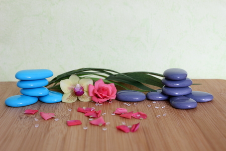 Decorative pebbles stacked in a zen life on a bamboo wooden board with a pink flower and an orchid on a green and foliage background