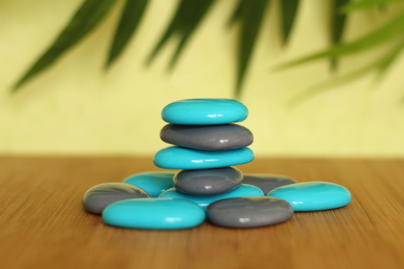 Stone pebble blue and gray posed on a wooden floor and clad in Zen lifestyle on green background Stock Photo