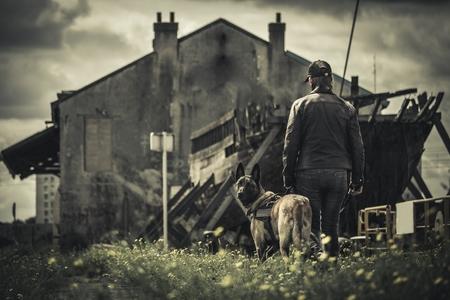 Una donna cammina con il suo cane nel paesaggio di montagna deserta e edificio abbandonato Archivio Fotografico - 85213848
